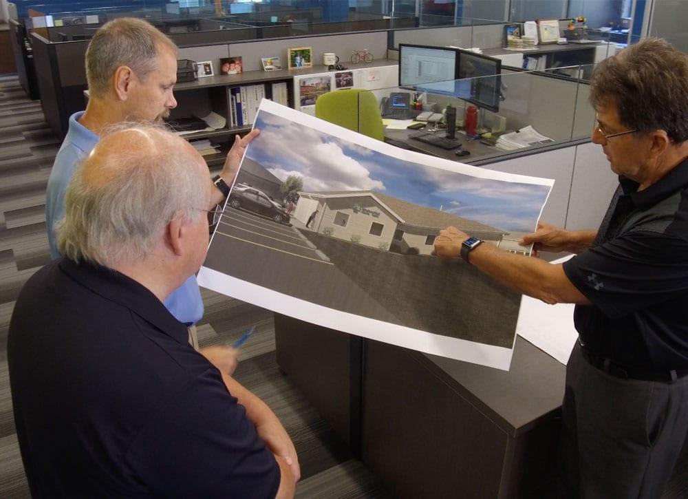 Men reviewing large rendering of building